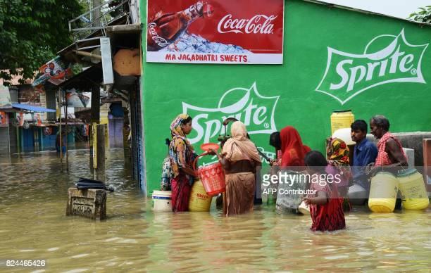 Indian flood victims gather to collect drinking water as they wade through flood waters in the Amta area of Howrah district around 55km west of...