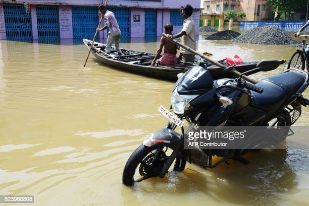 Indian flood victims on a boat cross a submerged road by a two wheeler parked in Shehagori village around 40km west of Kolkata on July 28 2017 The...