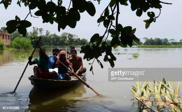 Indian flood victims on a boat make their way through flood waters after collecting relief materials in the Amta area of Howrah district around 55km...