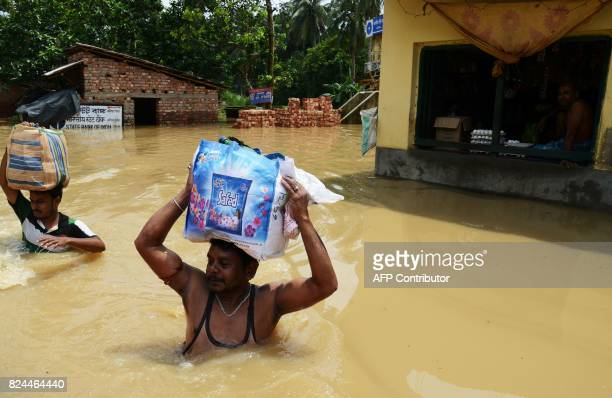 Indian flood victims wade through flood water after collecting relief materials in the Amta area of Howrah district around 55km west of Kolkata on...
