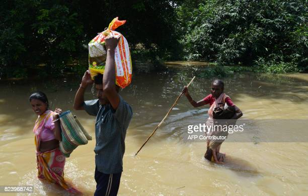 Indian flood victims wade through flood waters after collecting relief materials in Shehagori village around 40km west of Kolkata on July 28 2017 The...