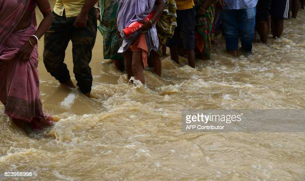 Indian flood victims wade through flood waters to collect relief materials in Chitnan village around 60 km West of Kolkata on July 28 2017 The Indian...