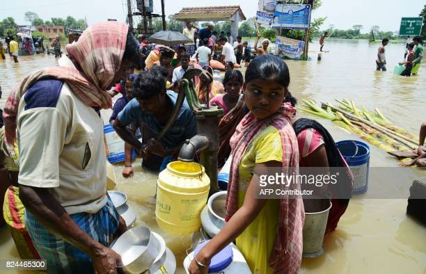 Indian flood victims with different containers stand in flood waters to collect dringking water in the Amta area of Howrah district around 55km west...