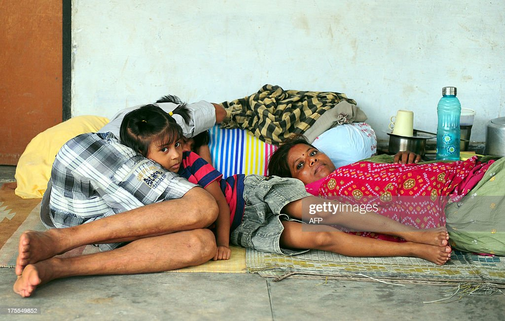 Indian flood-affected people rest at a local shelter in Allahabad on August 4, 2013. The monsoon, which covers the subcontinent from June to September and usually brings flooding, accounts for about 80 percent of India's annual rainfall.