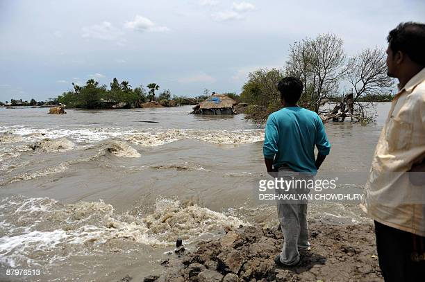 Indian floodaffected villagers watch a broken river bank in the village of Sandeshkhali some 100 kms southeast of Kolkata on May 26 2009 Bangladesh...