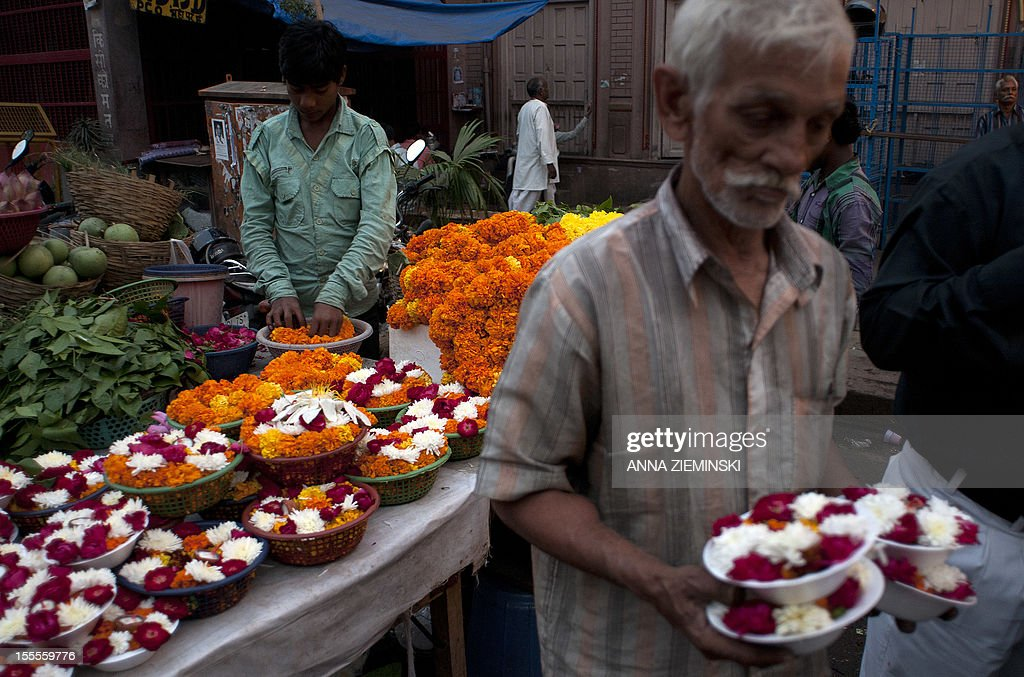 Indian flower-sellers arrange their goods outside a temple in New Delhi on November 5, 2012. The ruling Congress party has rolled out its big guns to defend the move to let the likes of Walmart set up shop in India, but they are confronting an alliance stretching across the political spectrum. Prime Minister Manmohan Singh's left-leaning government announced in September that it was lowering the bar for foreign firms to operate in sectors ranging from retail to insurance, in a bid to revive its fortunes before elections in 2014 but elsewhere in the country, a broad array of Congress opponents are vowing to scupper the changes. AFP PHOTO/Anna ZIEMINSKI