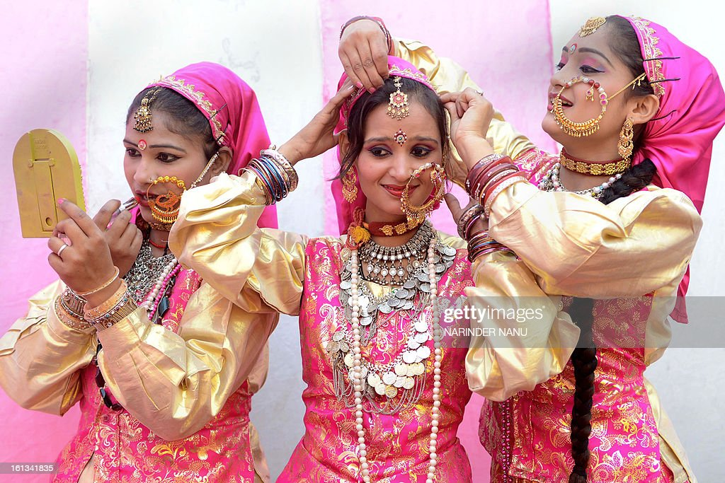 Indian folk dancers from Garhwal state of Uttarakhand, apply lipstick before performing a Garhwali folk dance during the annual function of Garhwali Yuva Bhrati Mandal in Amritsar on February 10, 2013.