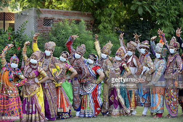 Indian folk dancers wearing face masks to raise awareness of ways to prevent the transmission of disease take part in a dress rehearsal in Ahmedabad...