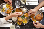 Two people sharing Indian food on a date.  An overhead shot of their hands reaching across the table and serving themselves the different dishes.