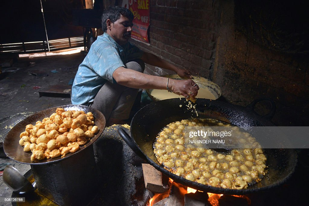 Indian food vendor Sham prepares moong dal ladoo in Amritsar on February 6, 2016. One plate with two laddo and accompanying pickles sells for INR 10 (around USD 0.14), and a days work selling them earns him around 300 Indian rupees (around USD 4.5 ). AFP PHOTO/ NARINDER NANU / AFP / NARINDER NANU