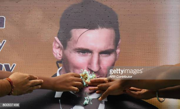 Indian football fans feed a piece of cake to a poster bearing the image of Argentine striker Lionel Messi during an event to celebrate his birthday...