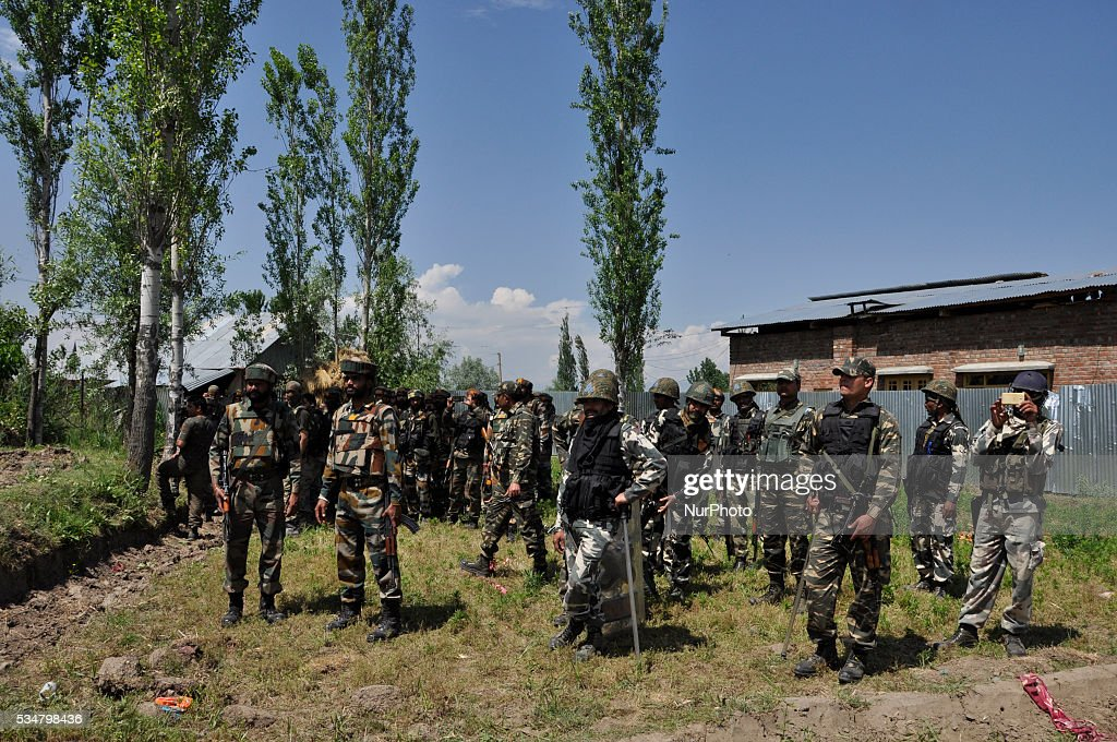 Indian forces look towards the Debris of damaged house were the gunbattle took place in Khonshipora 25 miles west of srinagar on May 27,2016.Two rebels were killed by indian forces during a brief gunfight.