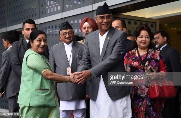 Indian Foreign Minister Sushma Swaraj shakes hand with Nepal's Prime Minister Sher Bahadur Deuba as his wife Arzu Rana Deuba looks on upon their...