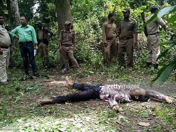 Indian Forestry Department officials stand beside the body of an alleged rhino poacher in Kaziranga National Park some 250 kms east of Guwahati on...