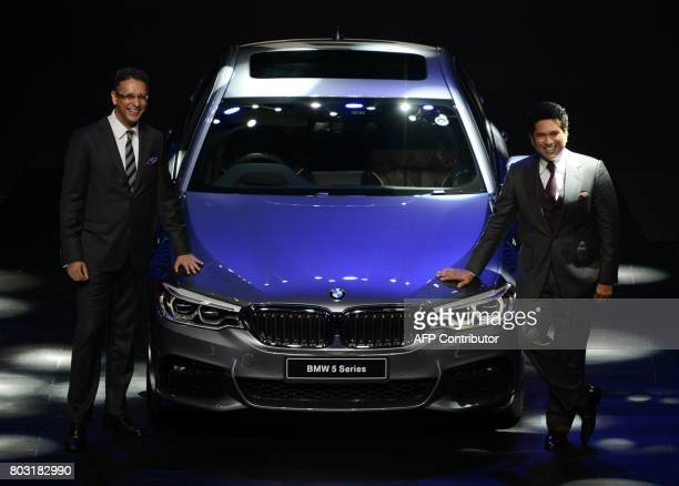 Indian former cricketer Sachin Tendulkar and BMW India President Vikram Pawah pose with the new BMW 5 series car during it's launch function in...
