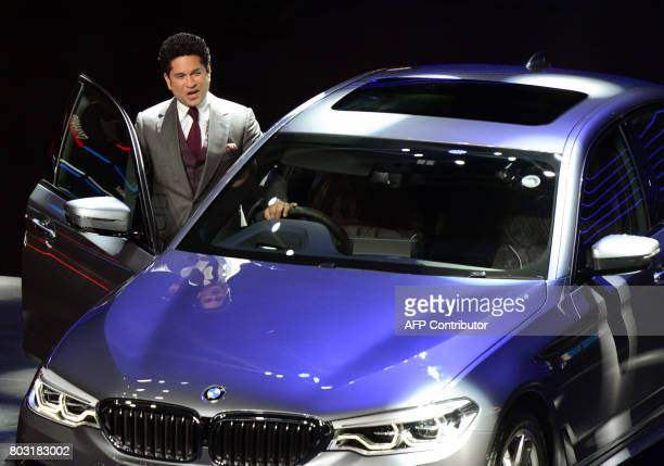 Indian former cricketer Sachin Tendulkar poses with the new BMW 5 series car during it's launch function in Mumbai on June 29 2017 PARANJPE