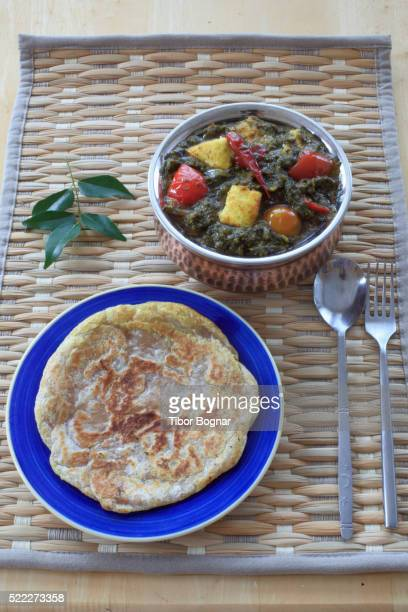 Indian fresh cheese with spinach, paratha bread,