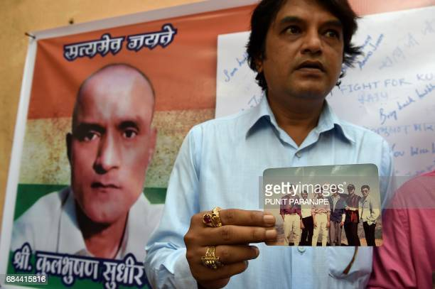 Indian friends of Kulbhushan Jadhav hold a photograph of them with Jadhav in the neighborhood where he grew up in Mumbai on May 18 2017 The UN's top...