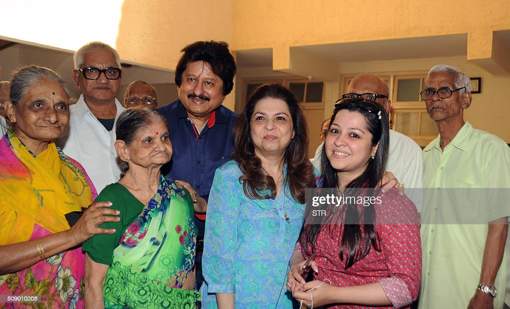 Indian Ghazal maestro Pankaj Udhas (C) with his wife Farida (centre R) and daughter Nayaab (2nd R) visit an old people's home where they marked his 35 years in show business in Mumbai on February 8, 2016. AFP PHOTO / AFP / STR