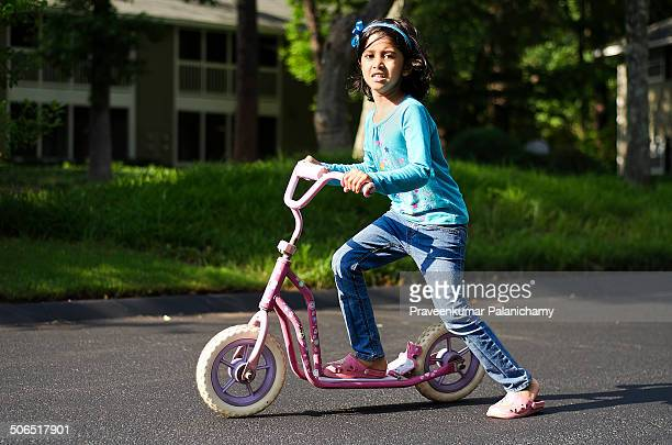 Indian girl child riding a scooter