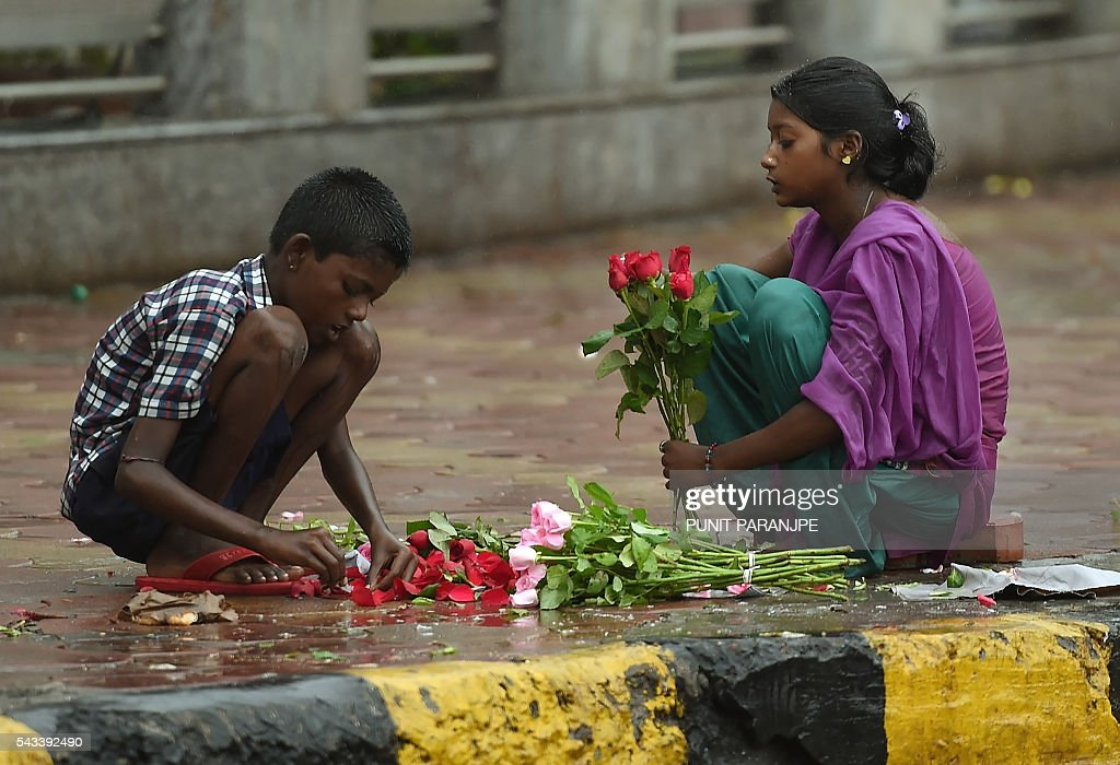 Indian girl children sort through roses for sale during rain showers in Mumbai on June 28, 2016. Annual monsoon rains have progressed to most parts of western and central India, easing fears of millions of desperate farmers after two straight years of drought, the weather department said. / AFP / PUNIT