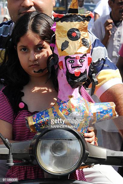 Indian girl Hirdaya Kapoor rides on her father Amit's scooter while carrying an effigy of Hindu demon King Ravana in Amritsar September 27 2009 on...