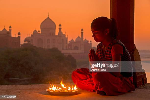 Indian girl praying with prayer lamp