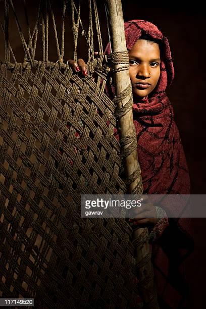 Indische Mädchen stehen hinter einer hand gewebten Jute-Kinderbett