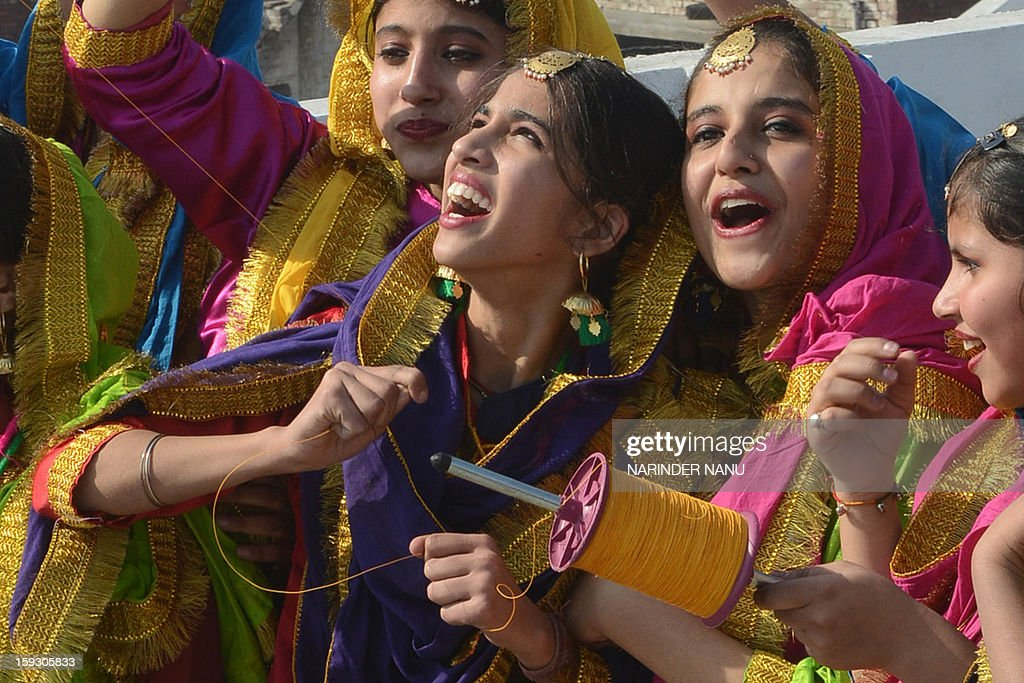 Indian girls dressed as Punjabi folk dancers gesture as they fly kites at a school in Amritsar on January 11, 2013 on the eve of Lohri festival. The Lohri festival is an annual thanks giving day and popular harvest festival in India, especially Northern India. AFP PHOTO/ NARINDER NANU