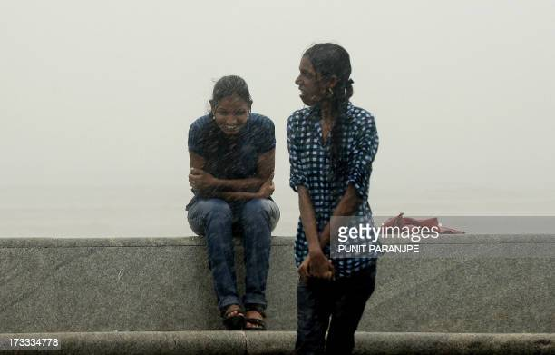 Indian girls enjoy heavy rain showers at the sea front in Mumbai on July 12 2013 The monsoon season which runs from June to September accounts for...