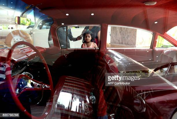 A Indian girls looks at a 1967 Chevrolet Impala at a vintage car display during Heritage Auto show in Chennai on August 20 2017 / AFP PHOTO / ARUN...
