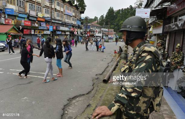 Indian girls plays as paramilitary troops stand guard at Chowkbazar area during an indefinite strike called by Gorkha Janamukti Morcha in Darjeeling...