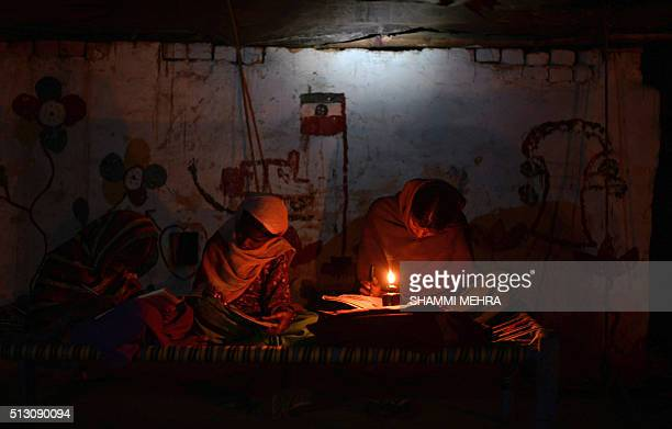 Indian girls study by candle light in a slum area without electric power in Phillaur around 50 km from Jalandhar on February 29 2016 India's...