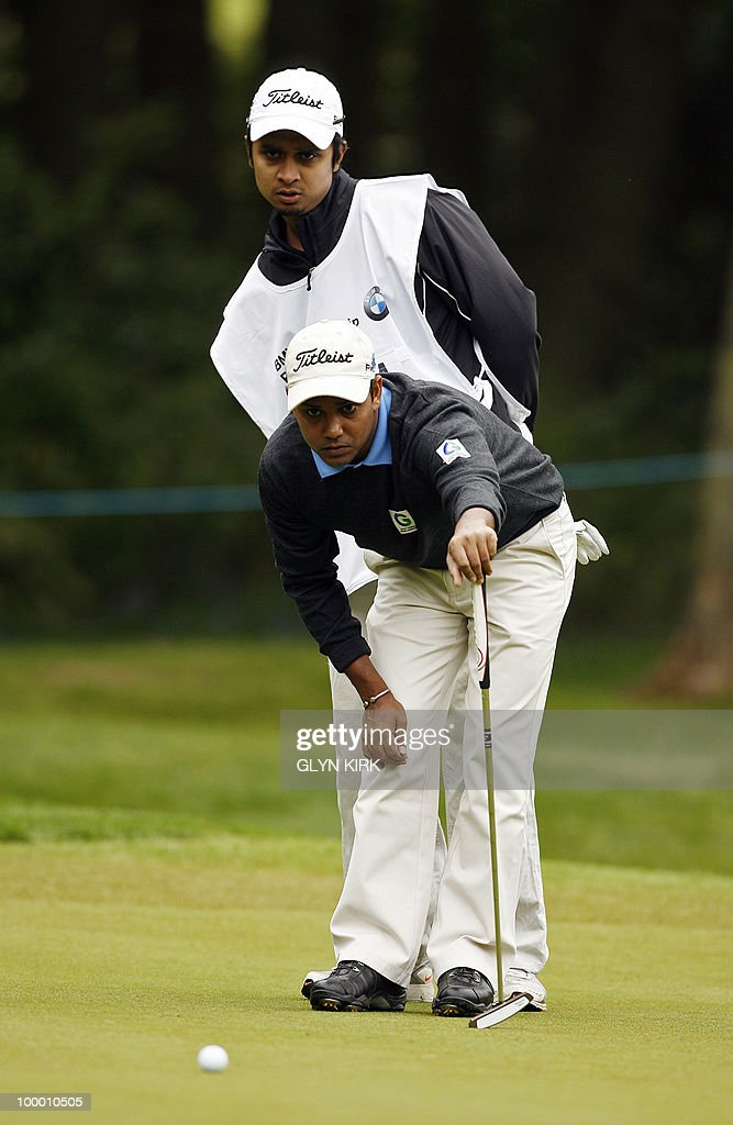 Indian golfer S.S.P Chowrasia (R) lines up his putt with the help of his caddy on the 1st green on the first day at the PGA Championship on the West Course at Wentworth, central England on May 20, 2010.