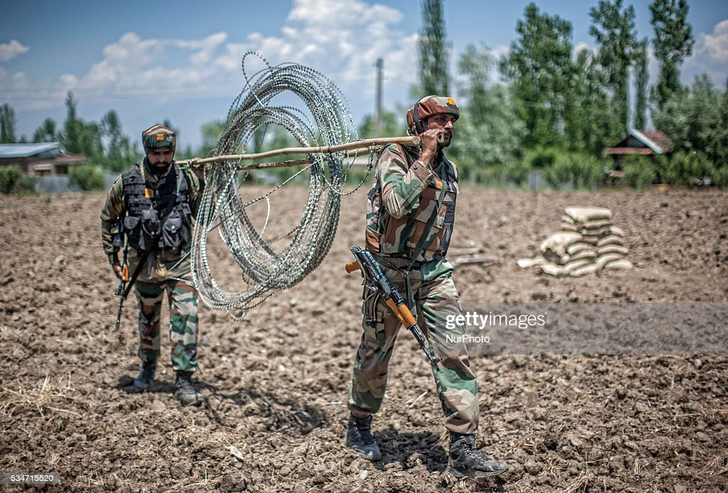 Indian government forces carry concertina razor wire after a gun battle between militants and Indian government forces on May 27, 2016 in Khonchpur, 40 kilometers (25 miles) west of Srinagar, the summer capital of Indian administered Kashmir, India. Six rebels and an Indian army soldier were killed in two separate gun battles in the north Kashmir today.