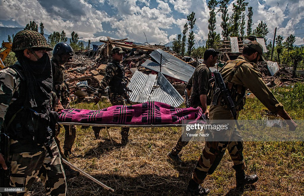 Indian government forces carry the body of local rebels killed in a gun battle between militants and Indian government forces, next to the ravaged residential house, on May 27, 2016 in Khonchpur, 40 kilometers (25 miles) west of Srinagar, the summer capital of Indian administered Kashmir, India. Six rebels and an Indian army soldier were killed in two separate gun battles in the north Kashmir just four days after the Indian police claimed to have gunned down two unidentified militants in Sarai Bala area of Srinagar, a claim contested by the locals who say they were just students putting up in the locality.