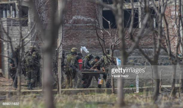 Indian government forces carry their wounded comrade during a heavy exchange of fire between suspected rebels and Indian government forces during a...