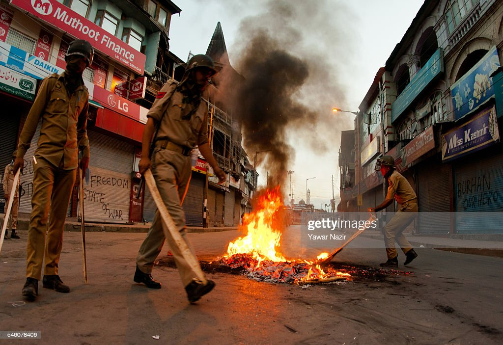 Indian government forces douse a burning tire left by the Kashmir protesters in the Ciity center during a curfew after 21 people were killed and more...