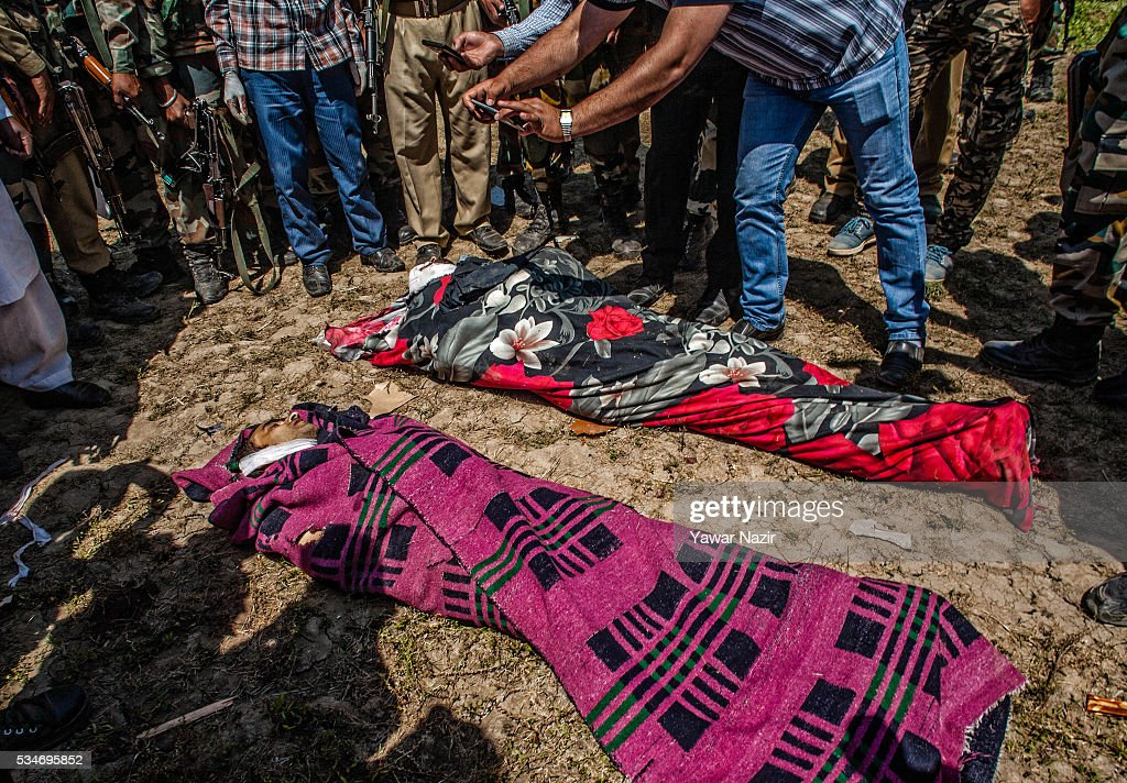 Indian government forces gather around the bodies of local rebels killed in a gun battle between militants and Indian government forces on May 27, 2016 in Khonchpur, 40 kilometers (25 miles) west of Srinagar, the summer capital of Indian administered Kashmir, India. Six rebels and an Indian army soldier were killed in two separate gun battles in the north Kashmir just four days after the Indian police claimed to have gunned down two unidentified militants in Sarai Bala area of Srinagar, a claim contested by the locals who say they were just students putting up in the locality.