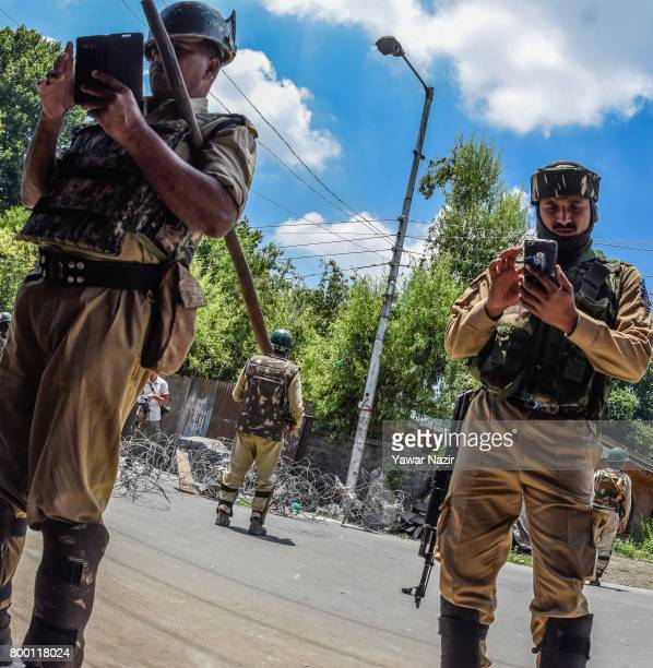 Indian government forces look at their cell phones as the stand guard during a curfew during a funeral on June 23 2017 in Srinagar the summer capital...