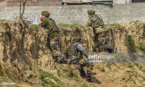 Indian government forces look towards a building being stormed by their comrades during a heavy exchange of fire between suspected rebels and Indian...
