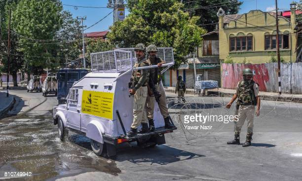 Indian government forces patrol the deserted roads in the old city during a curfew on the the first death anniversary of Burhan Wani a young rebel...