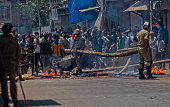 Indian government forces remove temporary barricades from a road as Kashmiri Muslim protesters shout anti Indian slogans during an anti Indian...
