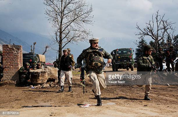 Indian government forces run for safety during a heavy exchange of fire between militants and them on February 21 2016 in Srinagar the summer capital...