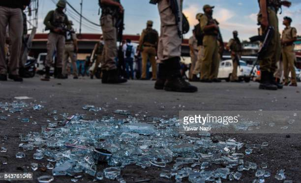 Indian government forces stand guard past strewn broken shards of a damaged vehicle after a grenade attack by suspected militants in a busy market on...