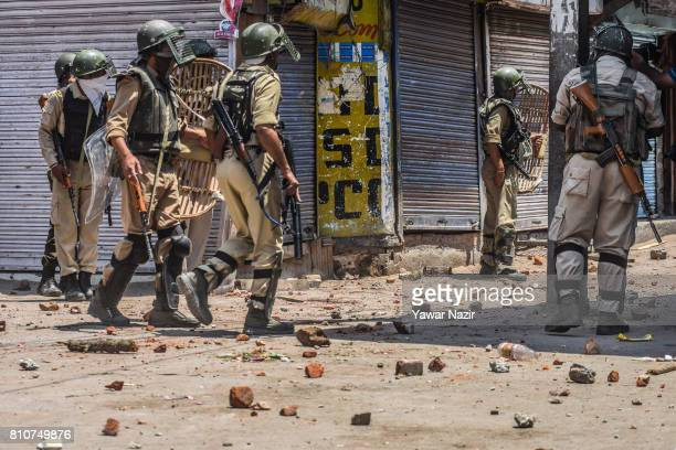 Indian government forces stand in the strewn stones thrown at them by Kashmiri Muslim protesters during a protest after Kashmiri Muslims defied...