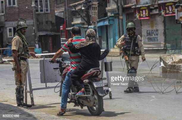 Indian government forces stop a Kashmiri motorcyclist during curfew on July 21 2017 in Srinagar the summer capital of Indianadministered Kashmir...
