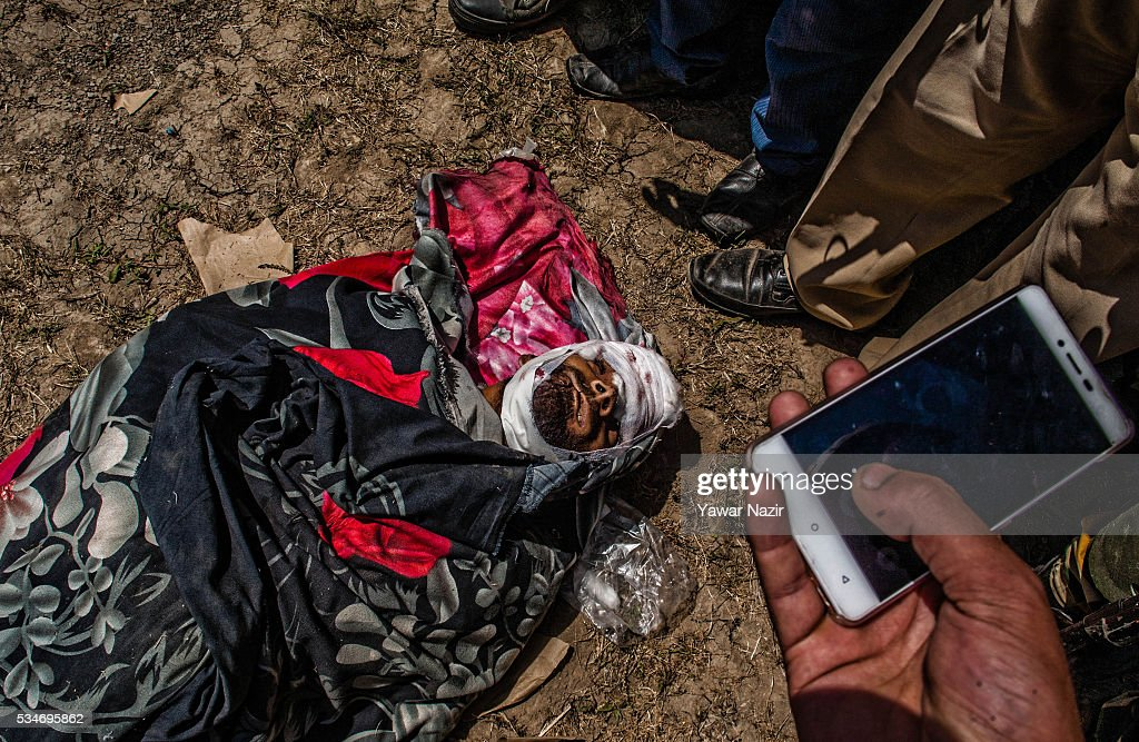 Indian government forces take pictures of with their mobile phone of local rebels killed in a gun battle between militants and Indian government forces on May 27, 2016 in Khonchpur, 40 kilometers (25 miles) west of Srinagar, the summer capital of Indian administered Kashmir, India. Six rebels and an Indian army soldier were killed in two separate gun battles in the north Kashmir just four days after the Indian police claimed to have gunned down two unidentified militants in Sarai Bala area of Srinagar, a claim contested by the locals who say they were just students putting up in the locality.