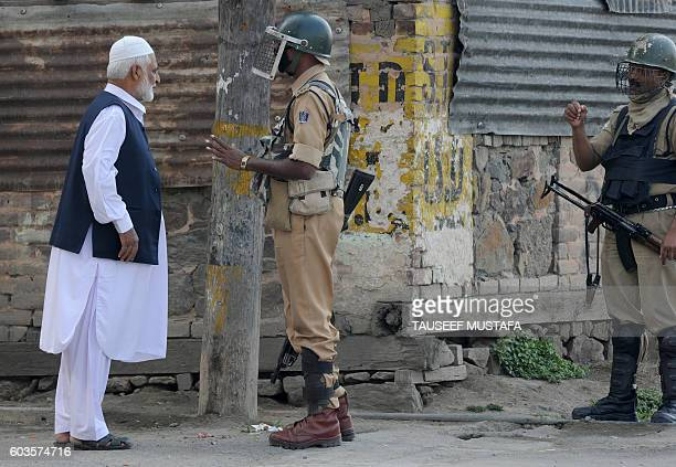 Indian government security personnel stop to check an elderly Kashmiri man during the Muslim festival of EidulAdha during a curfew in Srinagar on...