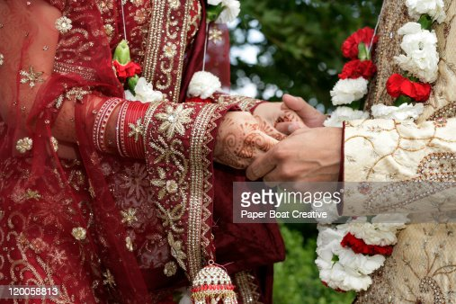 Indian groom holding the hands of his bride : Stock Photo